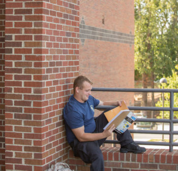 Male student seated outside reading.