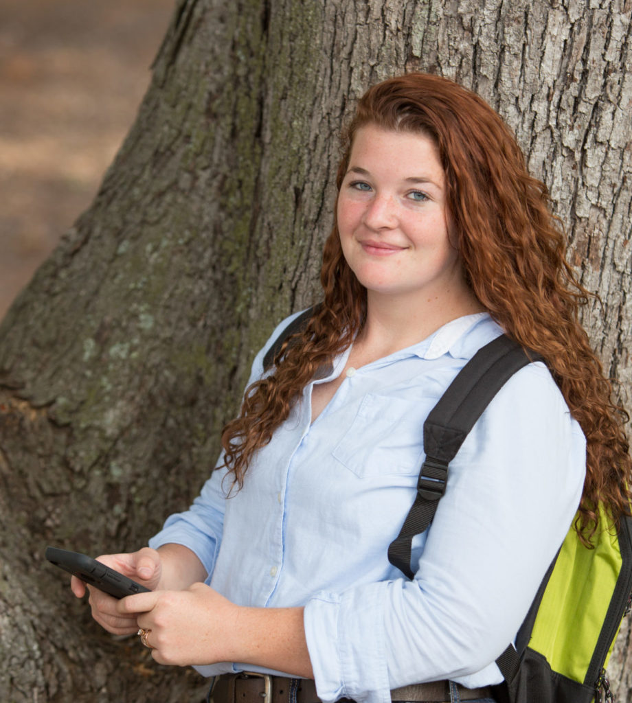 student with phone leaning on tree