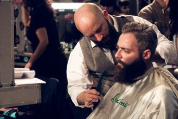 Barber trimming mans beard