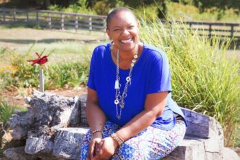 A Black woman smiling big with a silver necklace and a blue top with blue, purple, and white pants that have a floral design sitting on some rocks in a garden. There is a whirlygig red bird on a post next to her. She has a white fence running behind her in the distance which frames the photo nicely.