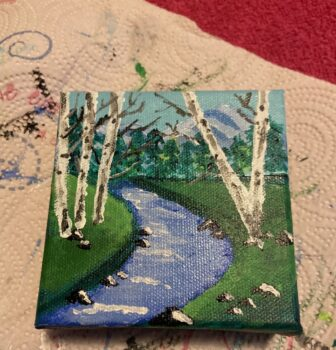 A painting of birch trees surrounding a flowing creek or river that has rocks along it with green grass and a blue sky with a line of trees in the background.